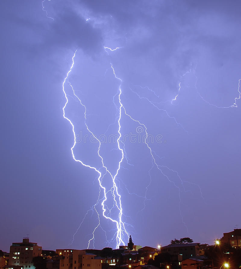 Lightning strike over dark blue sky in night city stock photos