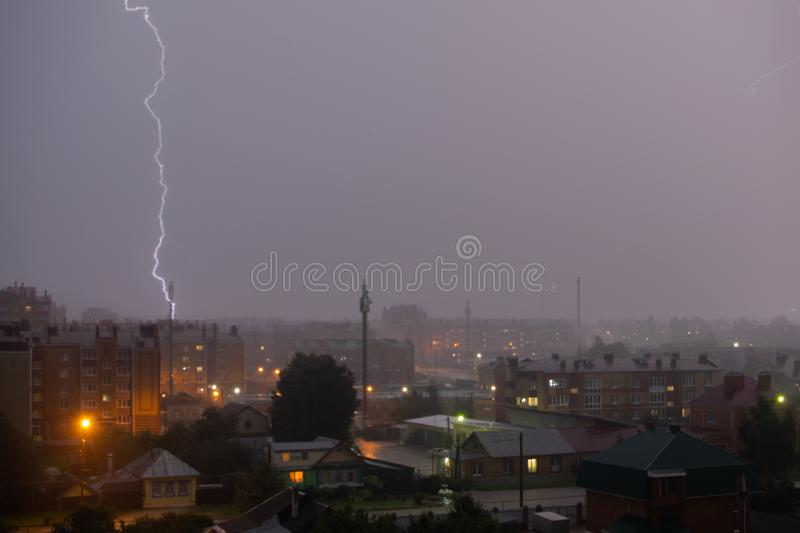 Lightning strike over dark gray sky in night city royalty free stock image