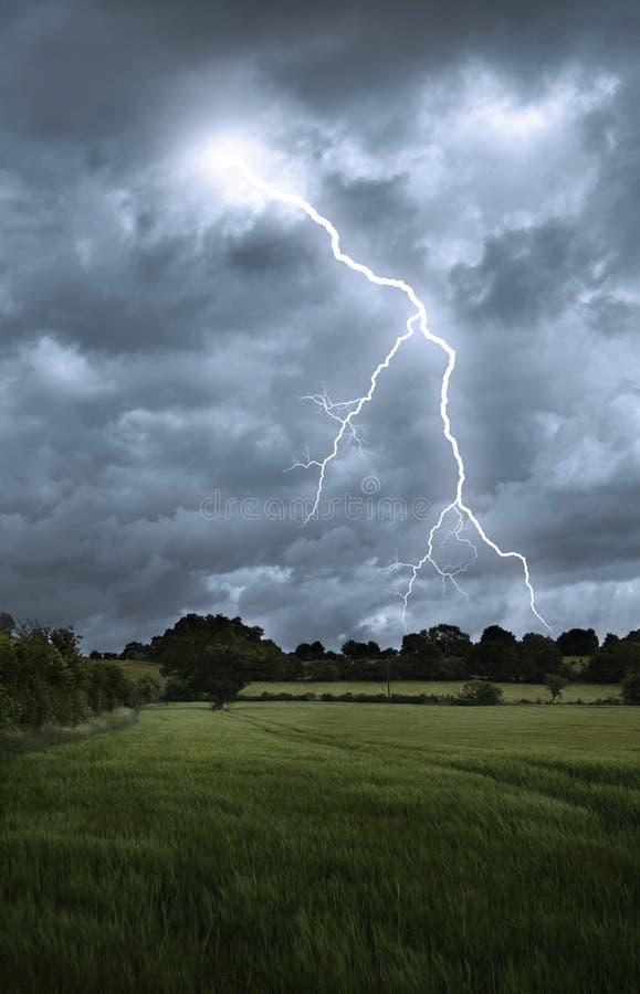 Lightning strike over field landscape stock photos