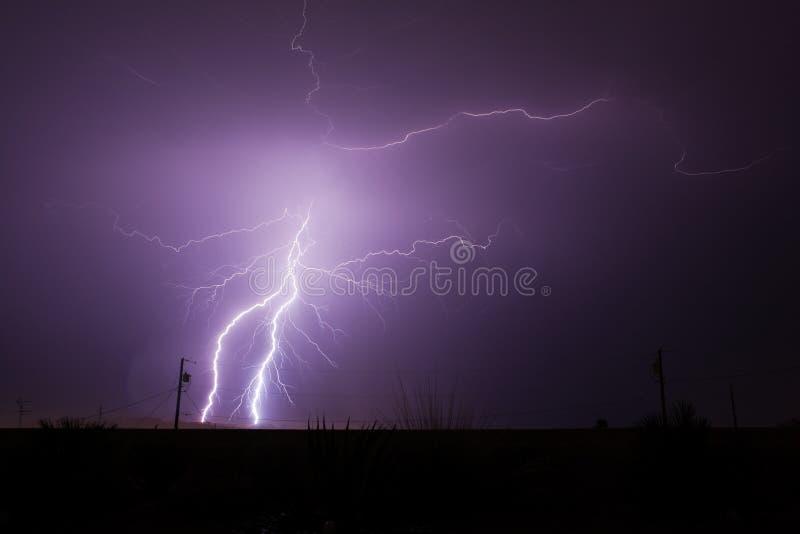 Lightning Strikes in Desert. Bolts of lightning strike and splinter off during a monsoon rain storm in the Arizona desert stock images