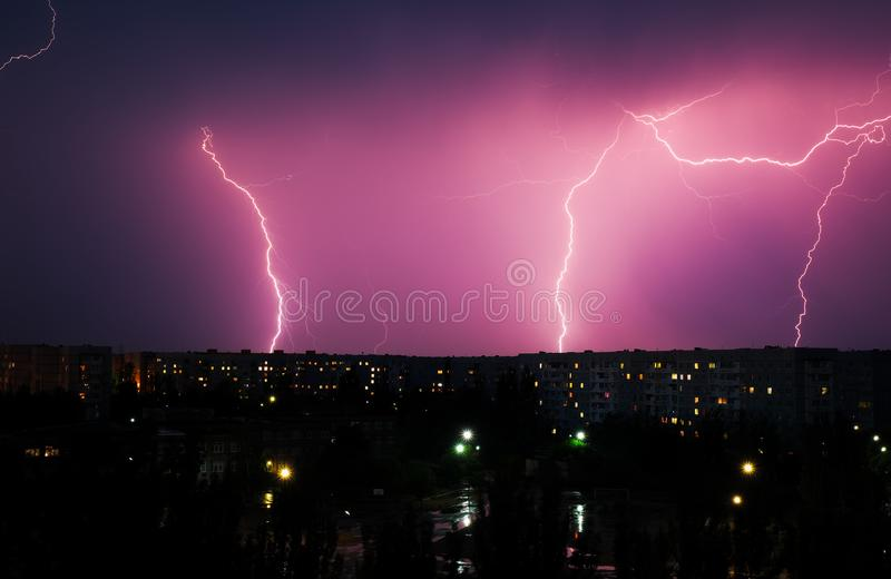 Lightning strikes down over the city at night. stock photo