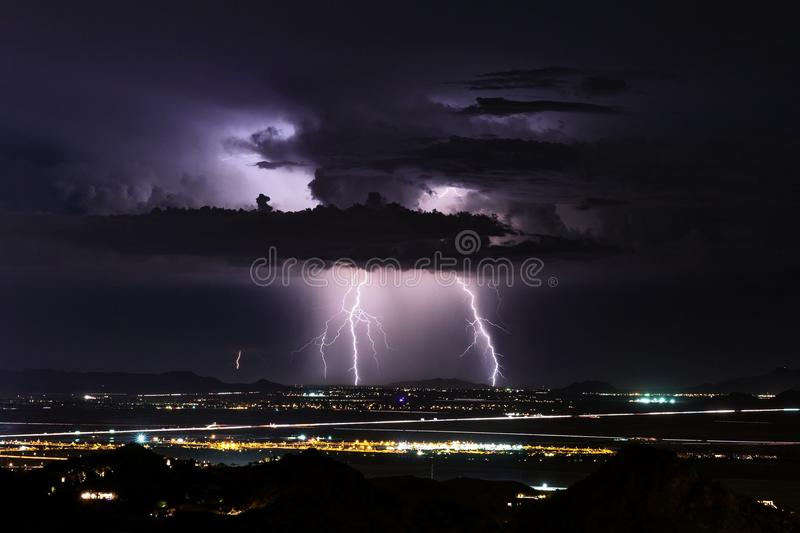 Lightning strikes during a monsoon thunderstorm. Lightning strikes from a distant thunder cloud during a monsoon storm over Phoenix, Arizona stock photo
