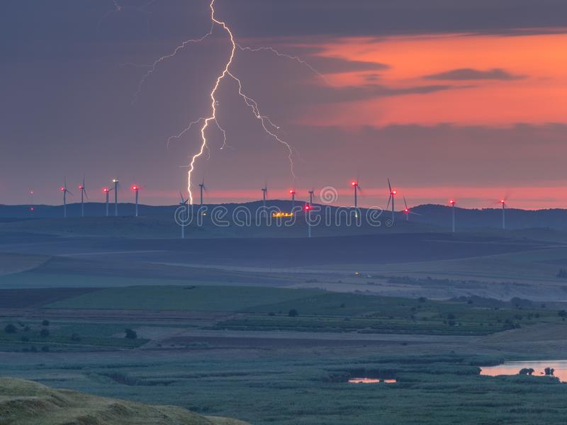 Lightning in the sunset sky over the hills with wind turbines and lake stock images
