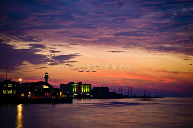 Lightouse Sunset. Colourful Lighthouse with sea and red sky and blue clouds at Sunset - Trieste - Italy 2007 royalty free stock photo