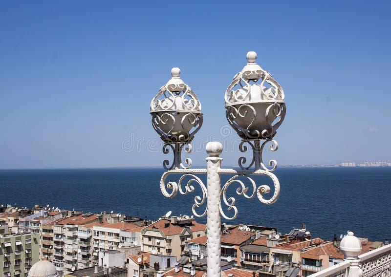 Lightpost sobre o elevador judaico, com construções de Izmir ao longo do golfo de Izmir foto de stock