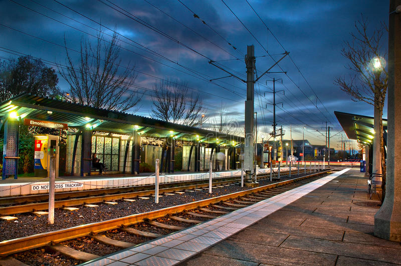 Lightrail station at sunset with rails and lights. Person on ben stock photo