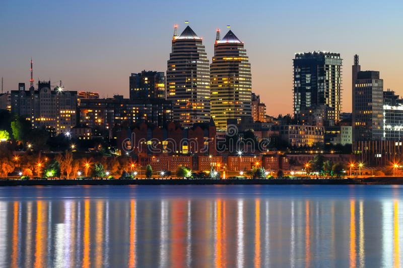The lights of the Beautiful tall buildings, skyscrapers, towers are reflected in the Dnieper River at sunset in the evening. The lights of the Beautiful tall stock image