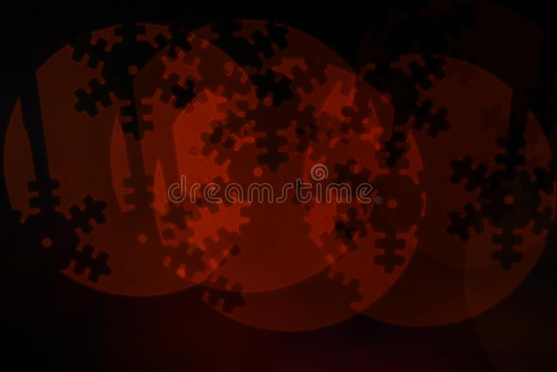 Lights of christmas garland blurred on black background. Christmas holiday decoration with silhouette of snowflake stock photography