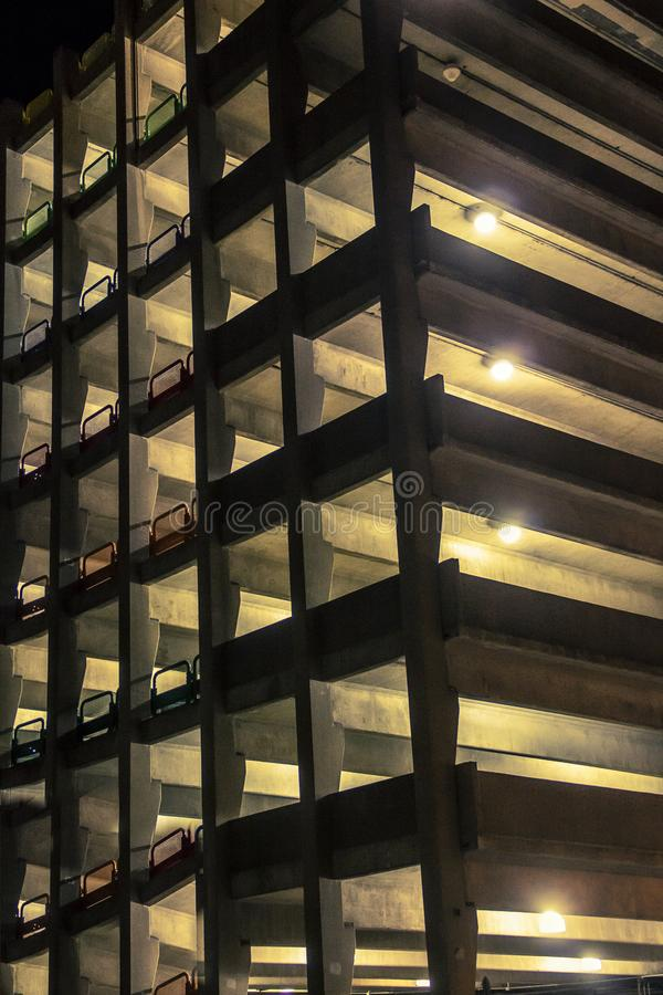 Lights glowing from a parking garage at night time stock photo