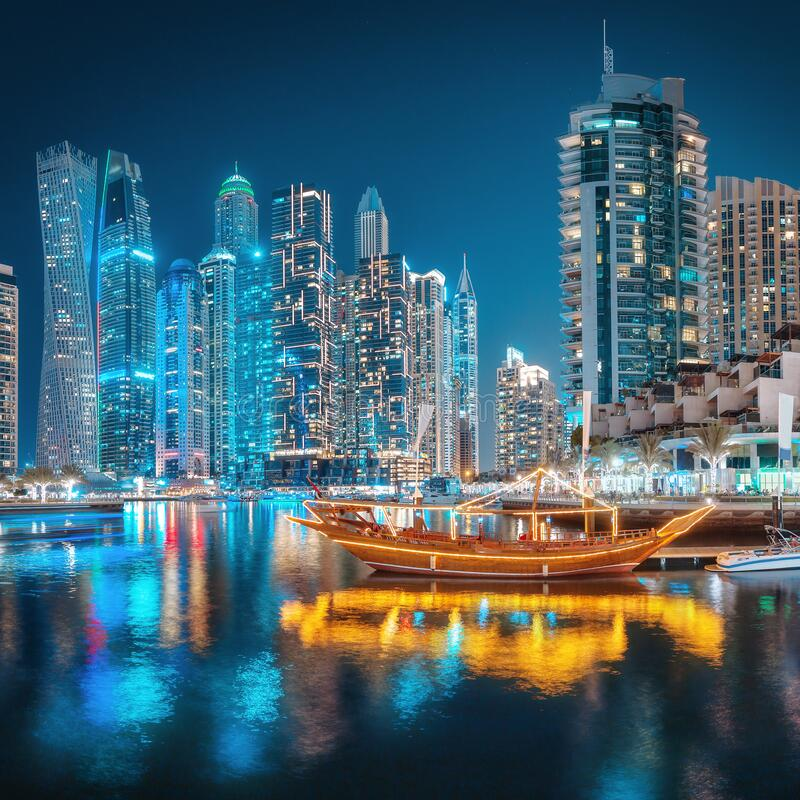 Free Lights Of The Night City In The Dubai Marina District. Stylized Ancient Arabic Ship Abra Dhow With Lights In The Stock Images - 172387544