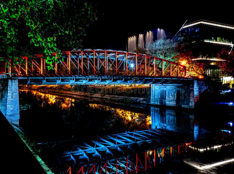 Lights on an old pedestal metal bridge designed by Gustave Eiffel and a view along the Bega River. In Timisoara near modern business building royalty free stock photos