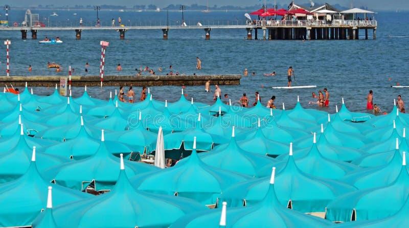 Lignano Pineta, Italien September 1 2018: rader av öppna paraplyer med havet och folket simmar eller tycker om i vattnet royaltyfri foto