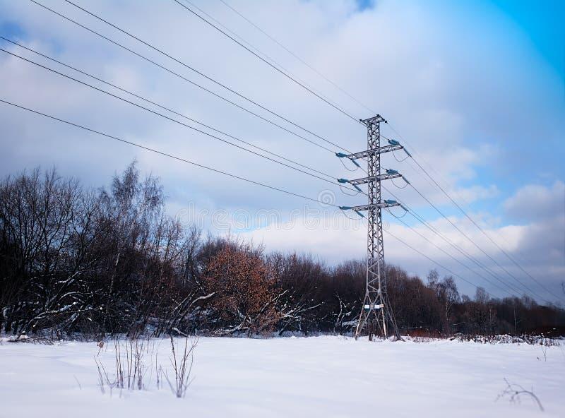 Ligne électrique d'hiver à l'arrière-plan de neige photos stock