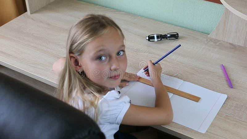 Ligne d'aspiration de petite fille par le crayon avec la règle dans le carnet De nouveau au concept d'école Jeune fille s'asseyan photo stock