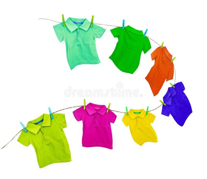 Ligne de blanchisserie avec les T-shirts colorés d'isolement sur un blanc photo stock