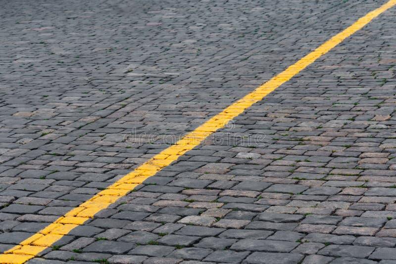 Ligne de repérage jaune sur le fond en pierre de trottoir, abstrait photo stock