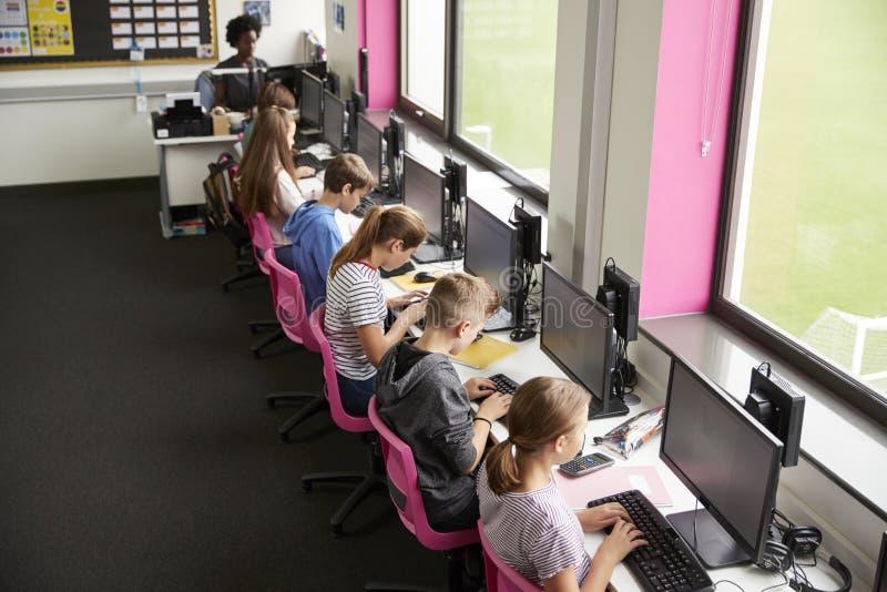 Ligne des étudiants de lycée travaillant aux écrans dans la classe d'ordinateur avec le professeur féminin In Background Shot de  photographie stock libre de droits