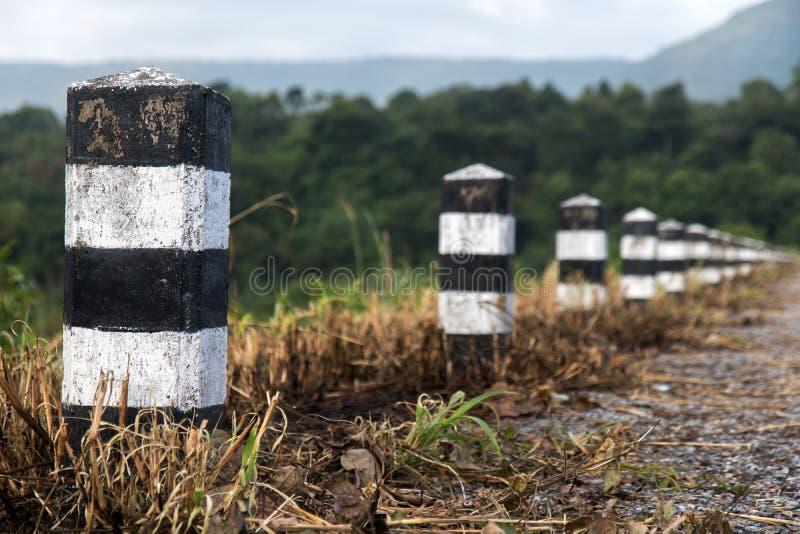 Ligne des bornes en pierre sur la route photo libre de droits