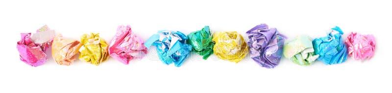 Ligne des boules de papier emiettées colorées d'isolement photographie stock