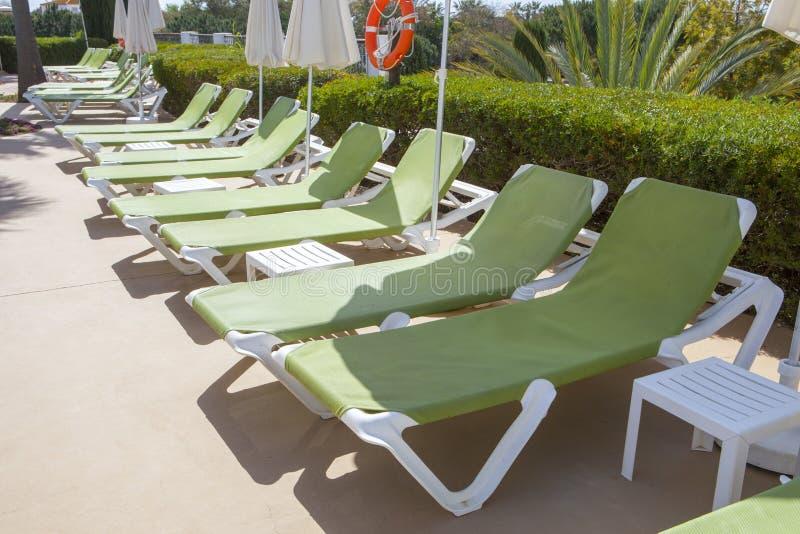 Ligne des chaises longues vertes sur la piscine photographie stock