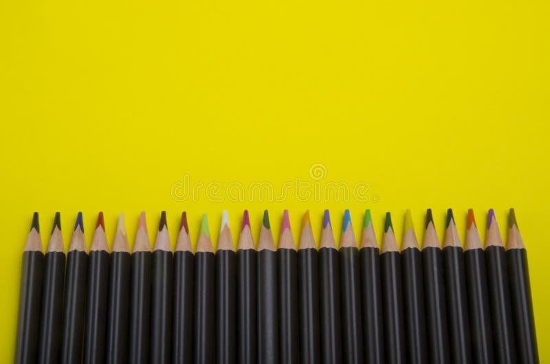 Ligne des crayons colorés sur le fond jaune image libre de droits