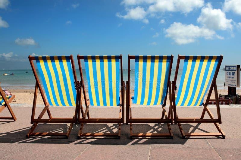 Ligne des deckchairs colorés sur la plage de Weymouth image libre de droits