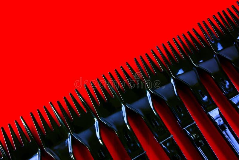 Ligne Des Fourchettes En Plastique Sur Le Rouge Photographie stock