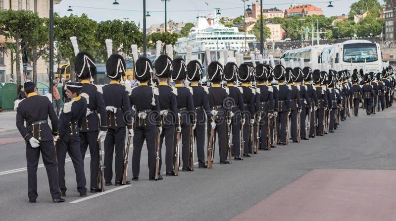 Ligne des gardes avec des chapeaux de fourrure sur une rue à Stockholm image libre de droits