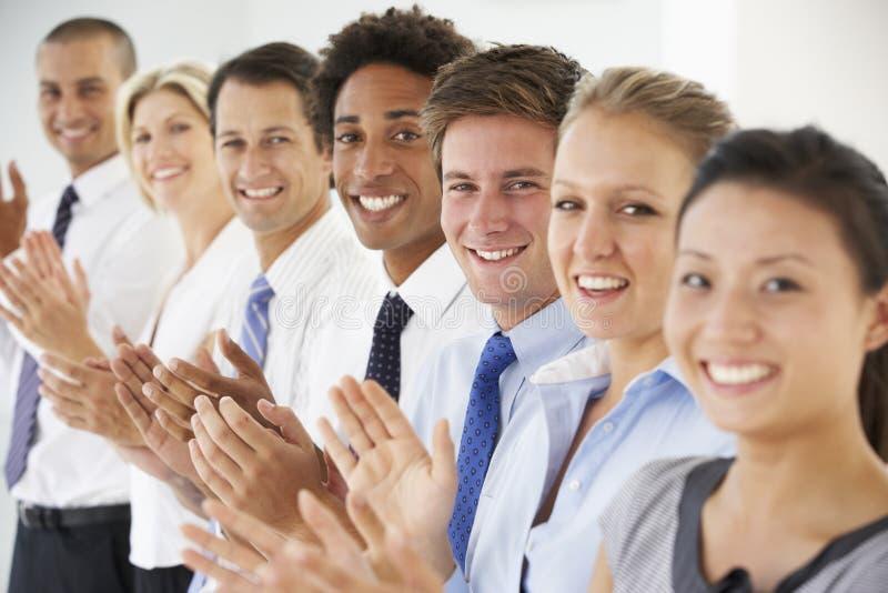 Ligne des gens d'affaires heureux et positifs d'applaudissements photos stock