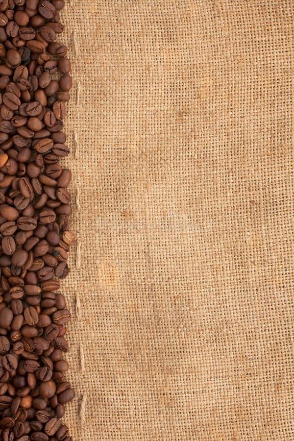 Ligne des grains de café et de la toile de jute photographie stock libre de droits