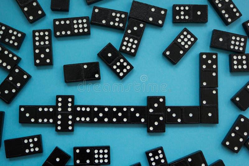 Ligne des morceaux de domino sur le fond bleu, vue à partir de dessus images stock