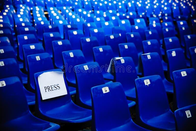 Ligne des présidences vides bleues dans une salle de conférences pour la presse images libres de droits