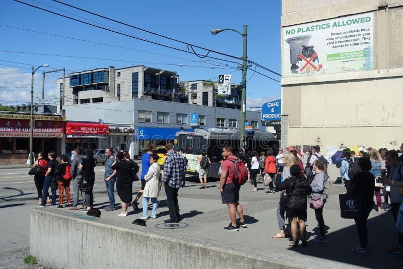 Ligne du ` s de banlieusard dans l'arrêt d'autobus du B-line 99 Vancouver photo libre de droits