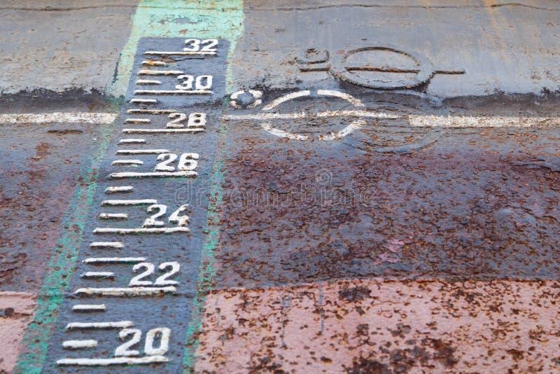 Ligne inscription de charge et échelle d'ébauche sur la coque rouillée du bateau dans l'amarrage sec pendant les réparations photo libre de droits