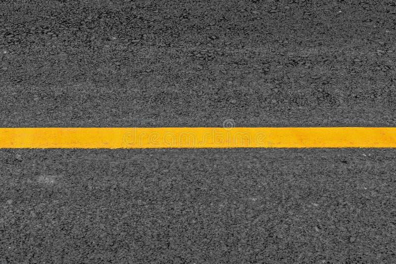 Ligne jaune sur le fond de route de texture d'asphalte avec grenu images stock