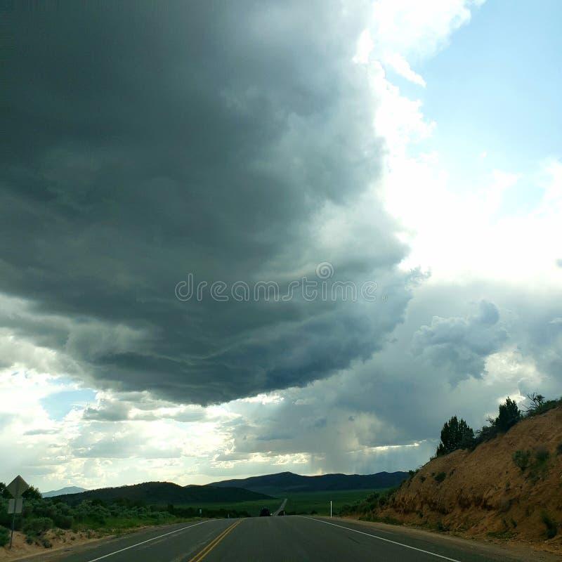 Ligne orageuse des nuages au-dessus d'une route rurale de montagne photo stock