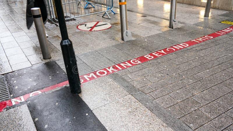 Ligne rouge sur le trottoir avec le texte NON-FUMEURS, signe près des piétons également de information ils entrent dans le secteu photos libres de droits
