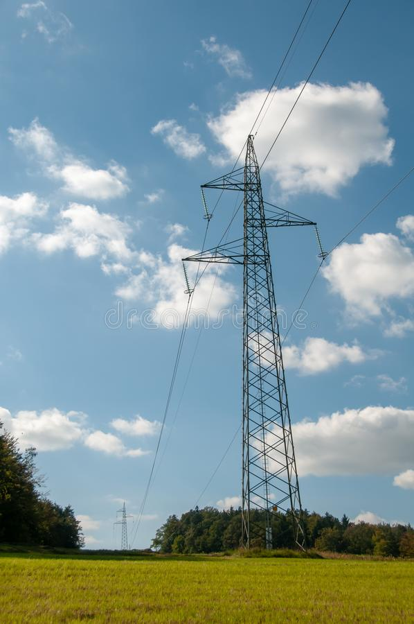 Lignes à haute tension et paysage innatural de pylônes de puissance sur le ciel bleu avec les nuages gonflés image stock