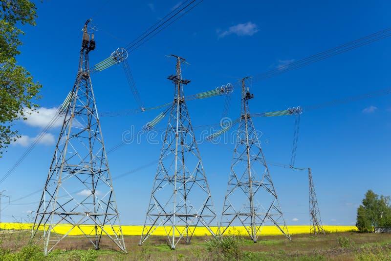 Lignes à haute tension et pylônes de puissance dans un paysage agricole plat et vert photos stock