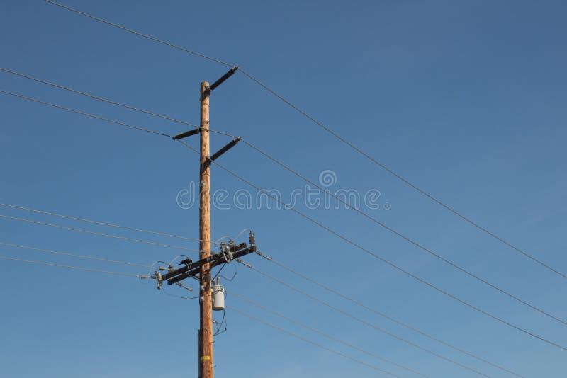 Lignes électriques et poteau à haute tension contre un ciel bleu profond photos stock