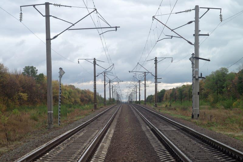 Lignes étirage ferroviaires d'automne au delà de l'horizon Paysage industriel obscurci d'octobre sous le ciel de plomb lourd image stock