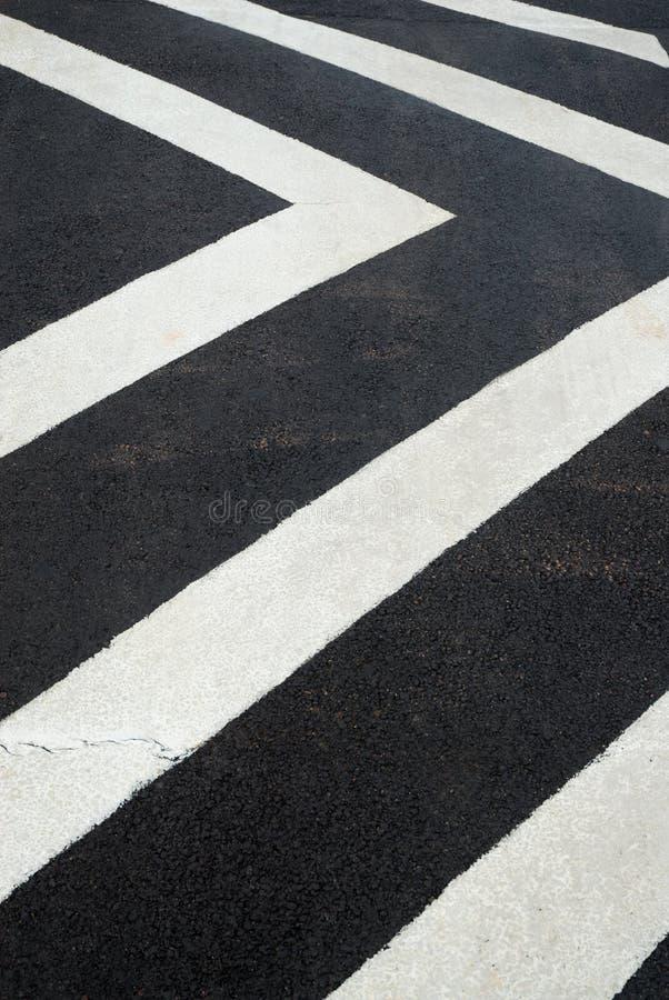 Lignes blanches de chevron sur une bosse de vitesse photo libre de droits