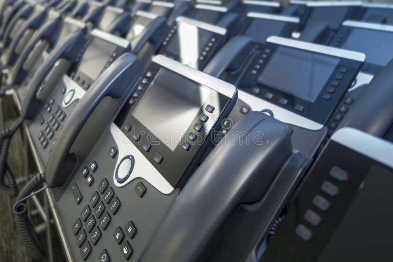 Lignes des téléphones d'affaires d'IP de bureau gris et des téléphones argentés prêts pour la télécommunication d'affaires photographie stock
