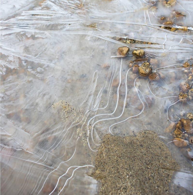 Lignes et courbes de glace dans l'étang avec le sable et les roches images libres de droits
