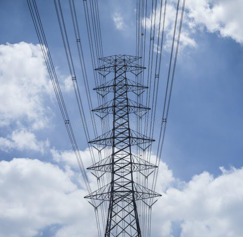 Lignes et pylône de transmission de l'électricité silhouettés contre le ciel bleu et le nuage, tour à haute tension photos stock