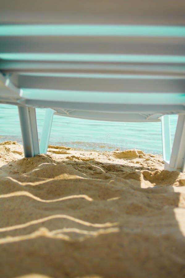 Ligstoel die zich op de pijler door van de overzeese het strand lichtenzon bevinden stock foto's