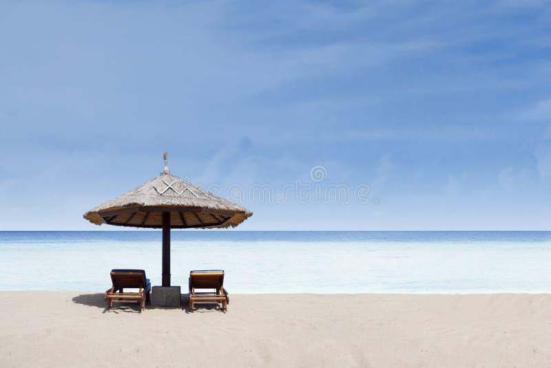 Ligstoel en paraplu op wit zand stock foto's