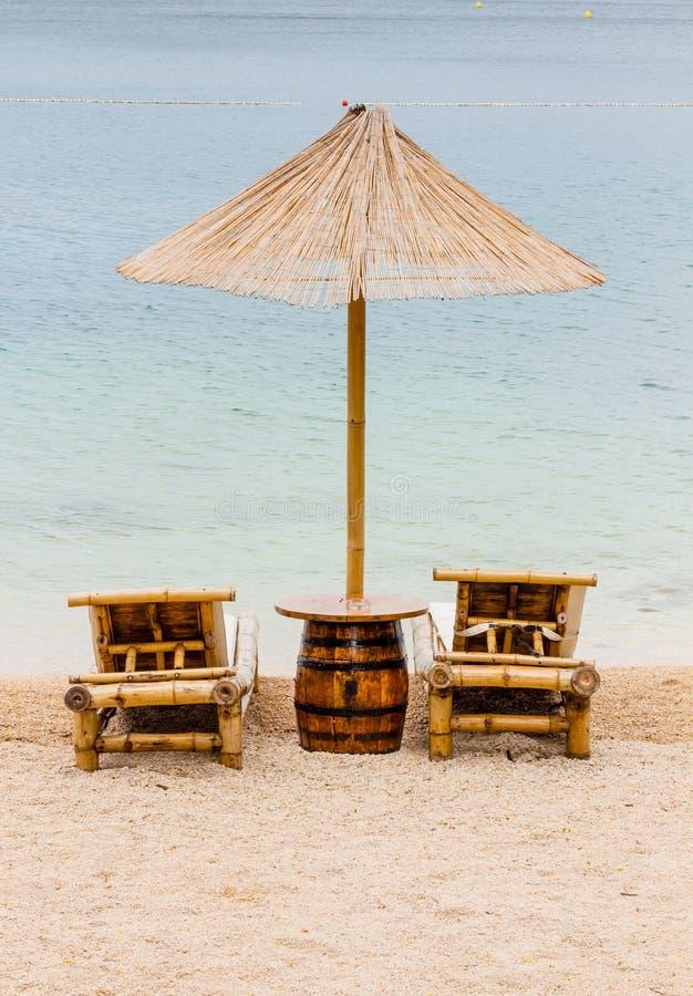 Ligstoel en paraplu op zandstrand Concept voor rust, ontspanning, vakantie, kuuroord, toevlucht royalty-vrije stock afbeeldingen