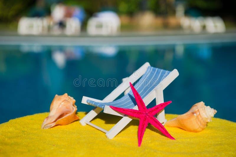 Ligstoel en shells bij zwembad stock afbeeldingen