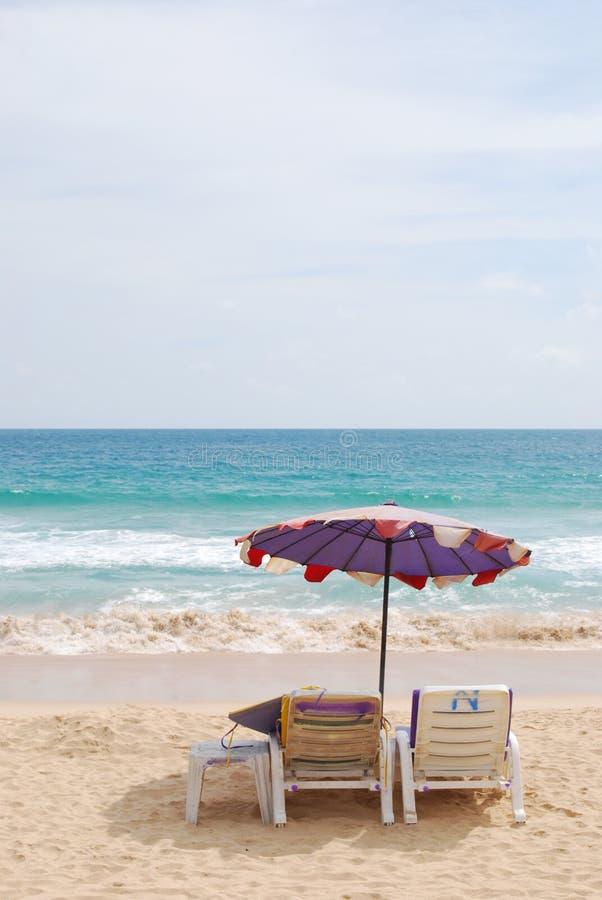 Ligstoel en witte paraplu op strand royalty-vrije stock fotografie